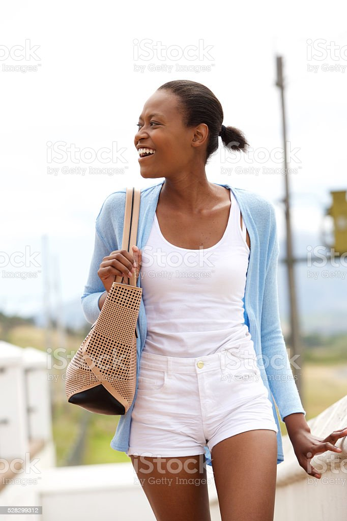 Happy young african lady walking outdoors stock photo