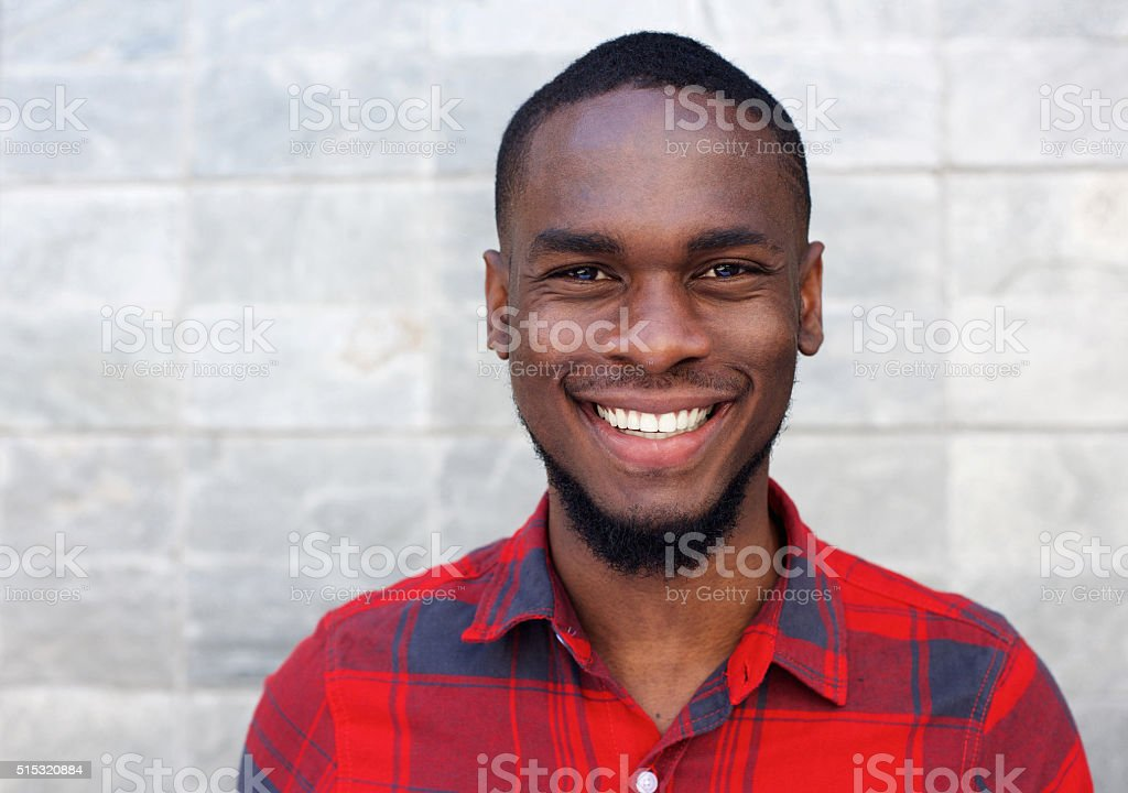 Happy young african man smiling against gray wall stock photo