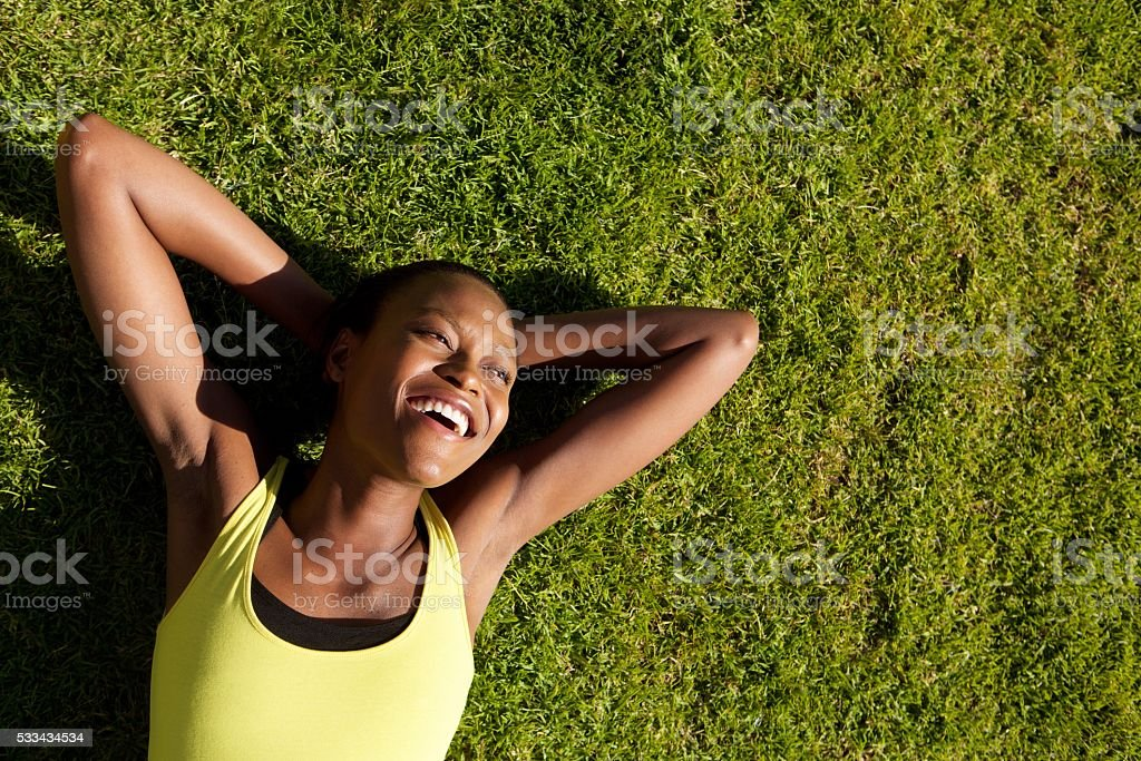 Happy young african woman resting on grass after workout stock photo