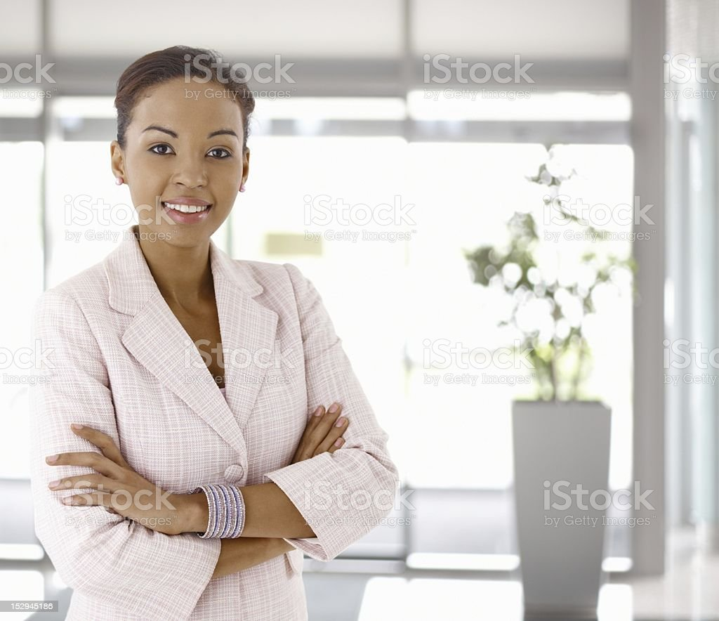 Happy young afro-american woman in office lobby stock photo
