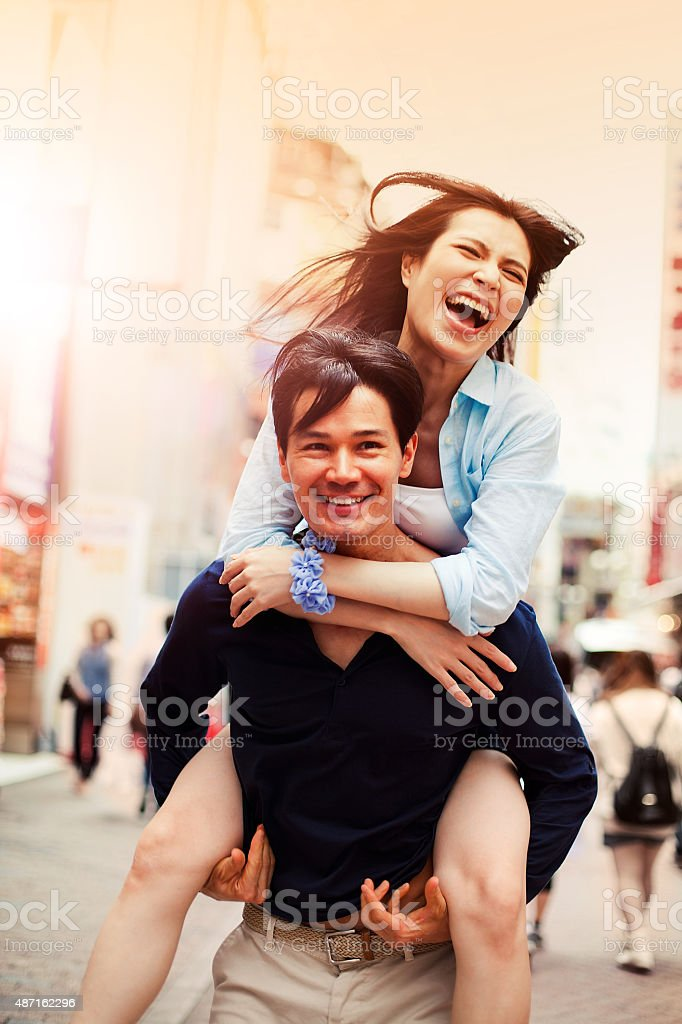Happy young asian couple having fun with piggy back stock photo