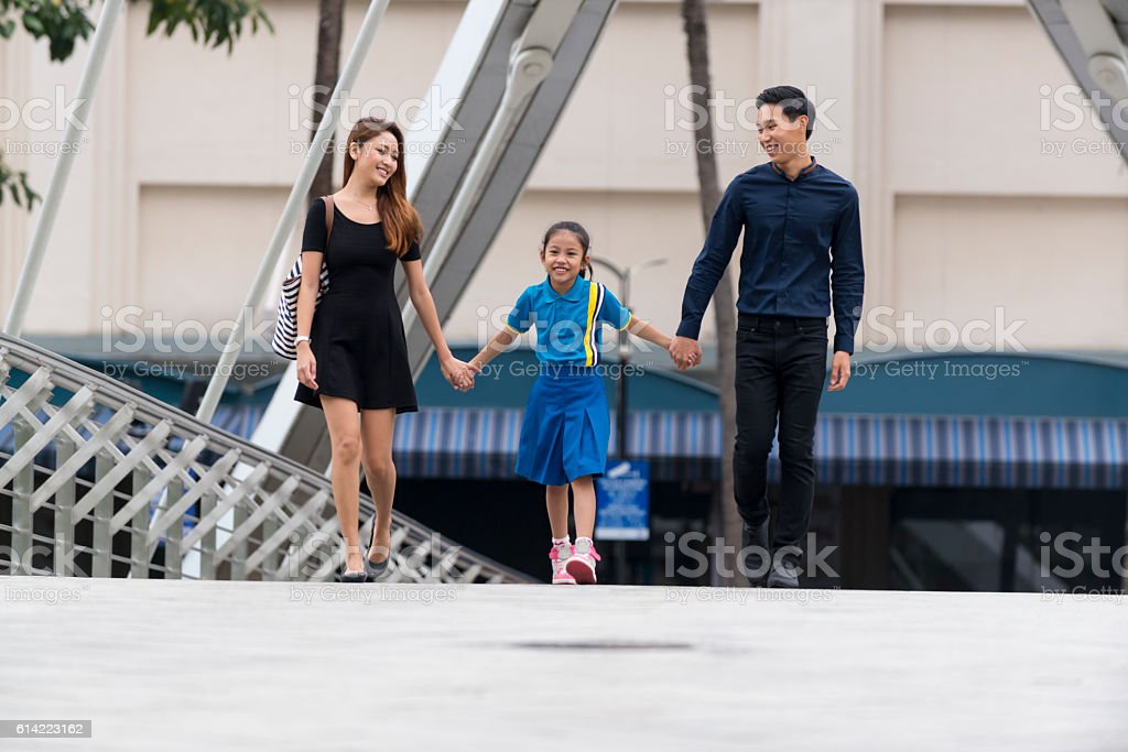 Happy Young Asian Family Strolling in The City Park stock photo
