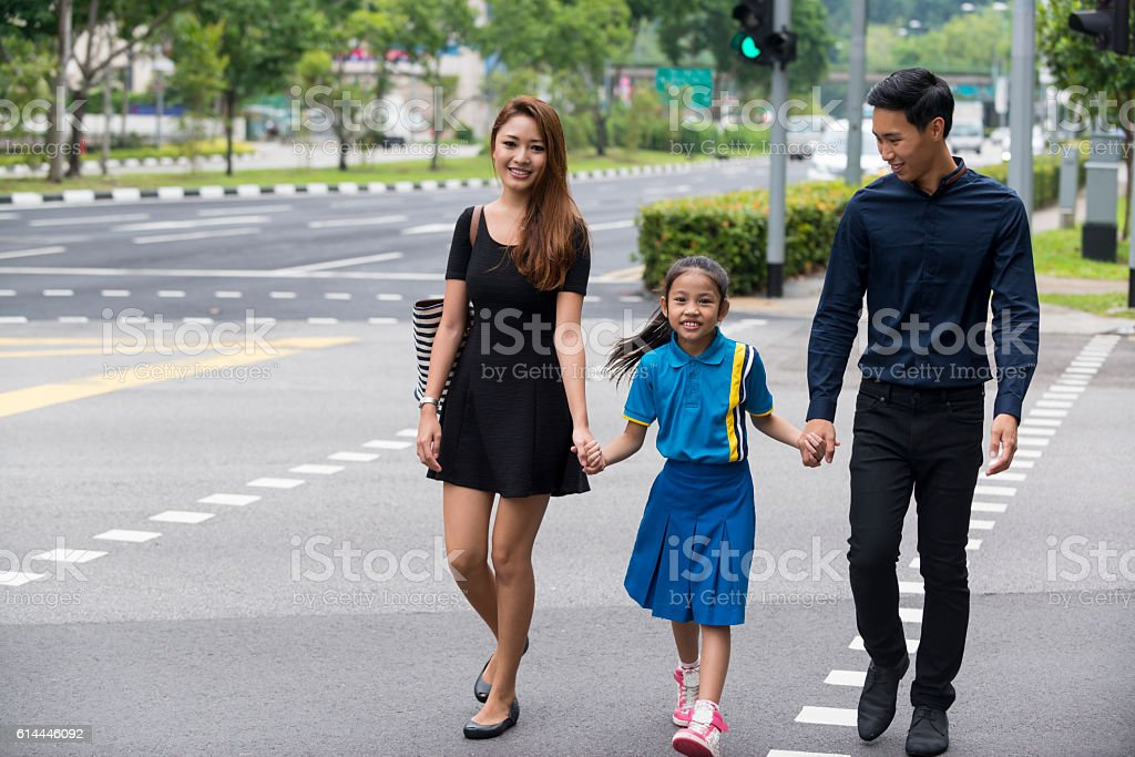 Happy Young Asian Family Walking on Pedestrian Crossing stock photo