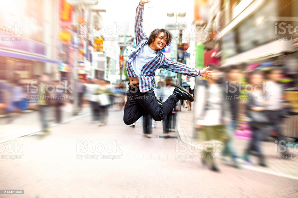 Happy young asian man jumping in Shibuya on the street stock photo