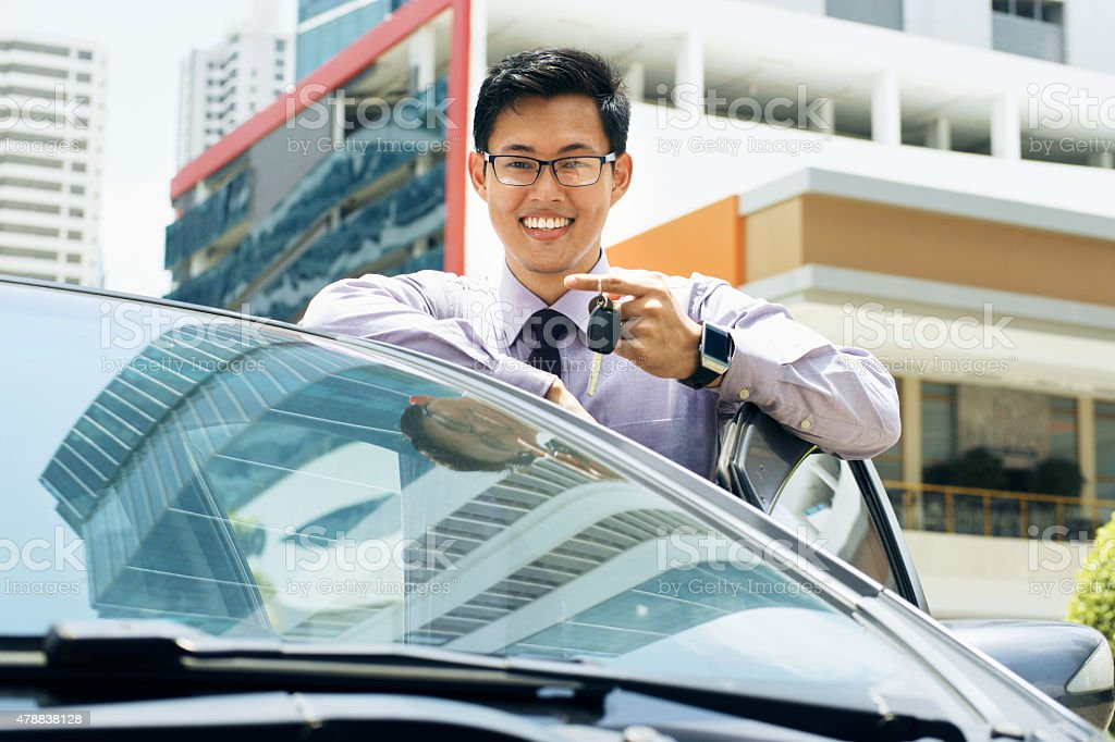Happy Young Asian Man Smiling Showing Keys Of New Car stock photo
