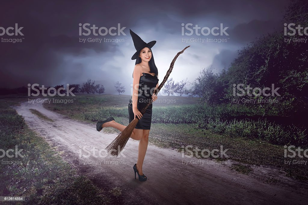 Happy young asian witch with a broom getting ready to stock photo