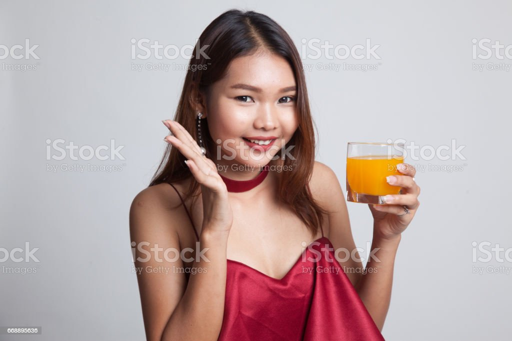 Happy Young Asian woman drink orange juice. stock photo