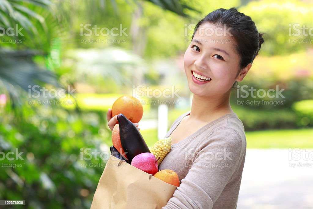 happy young asian woman holding vegetable and fruit royalty-free stock photo