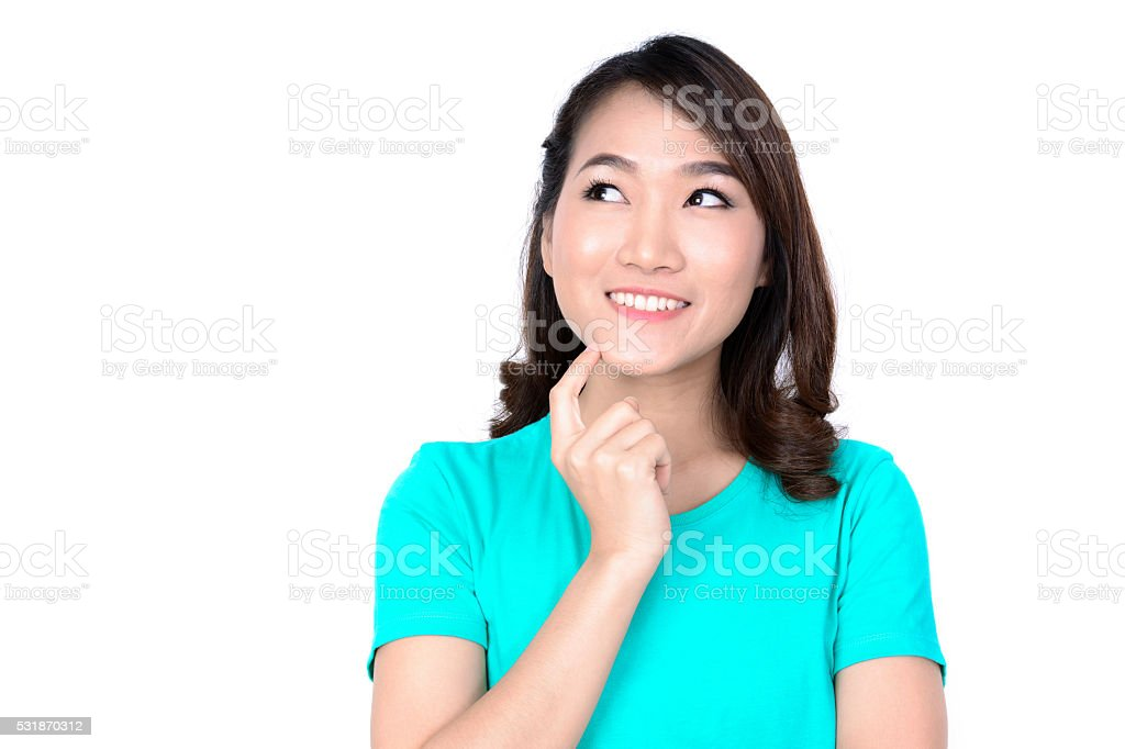 Happy young Asian woman thinking while looking up stock photo