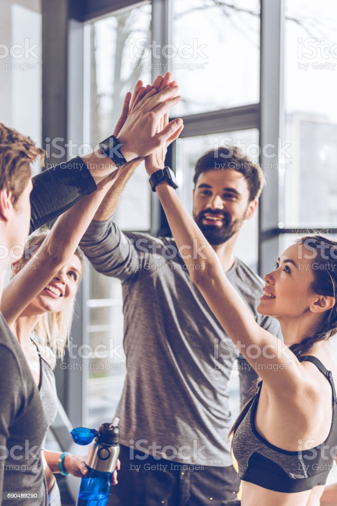 Happy young athletic people in sportswear giving high five in gym stock photo