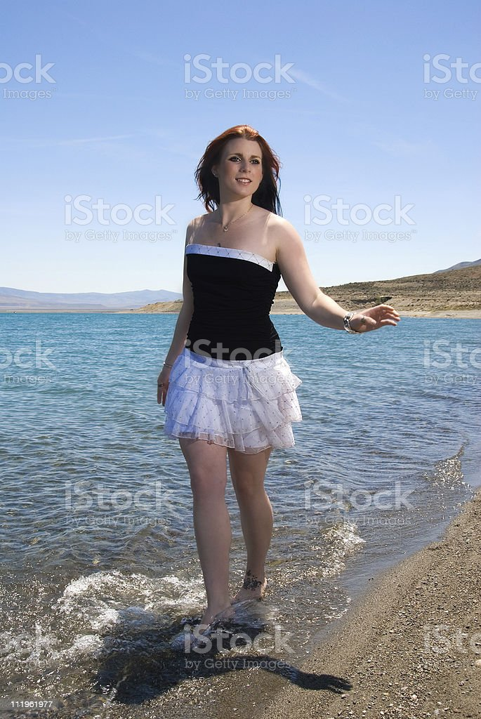 Happy young beautiful redhead walking on the edge of  water royalty-free stock photo