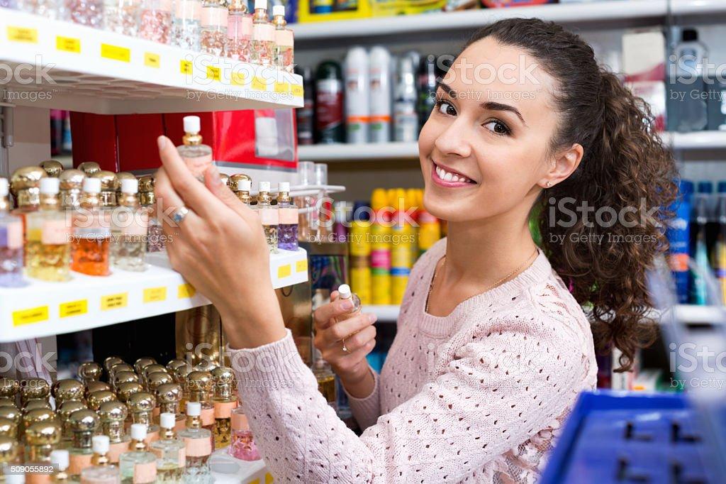 Happy young beautiful woman choosing fragrance stock photo