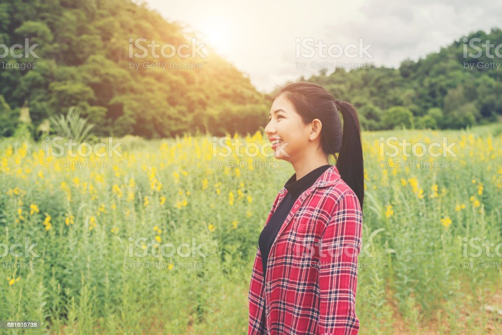 Happy young beautiful woman enjoying summer in yellow flower field at sunset. stock photo