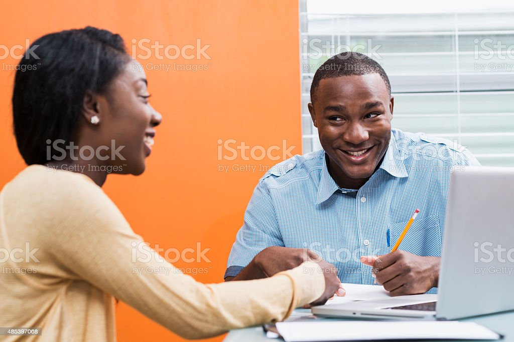 Happy young black couple sitting at table with laptop stock photo