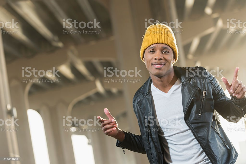 Happy young black man in city wearing yellow beanie stock photo