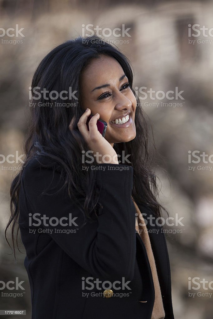 Happy young black  teenage girl using a mobile phone royalty-free stock photo