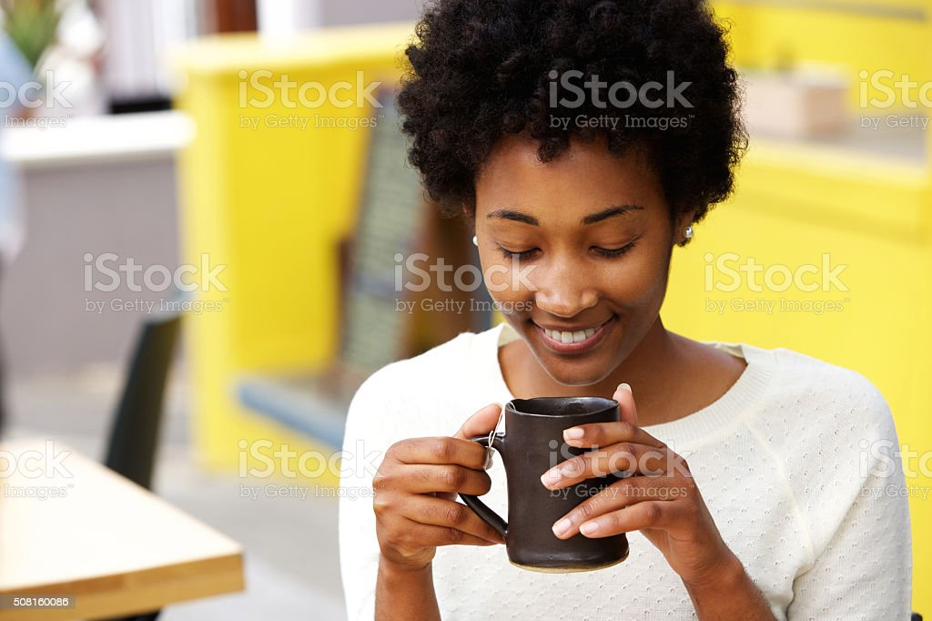 Happy young black woman drinking coffee stock photo