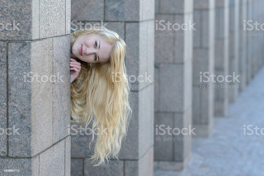 happy young blond girl looking out from between columns stock photo