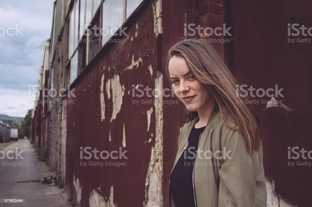 Happy young blond woman in ruined background stock photo