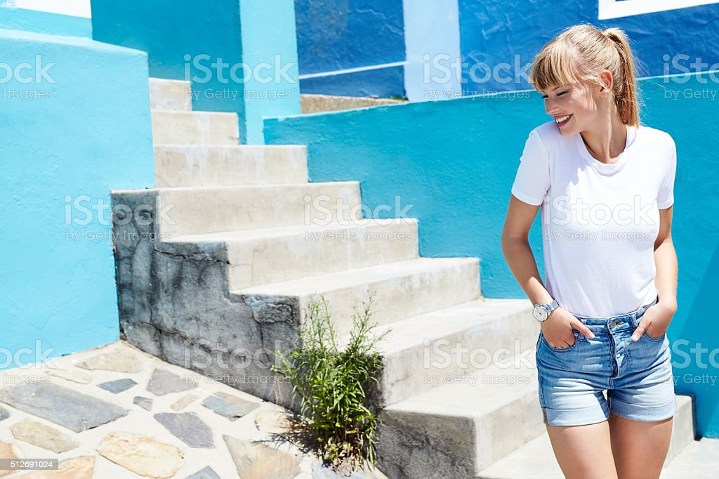 Happy young blond woman in shorts and t-shirt stock photo