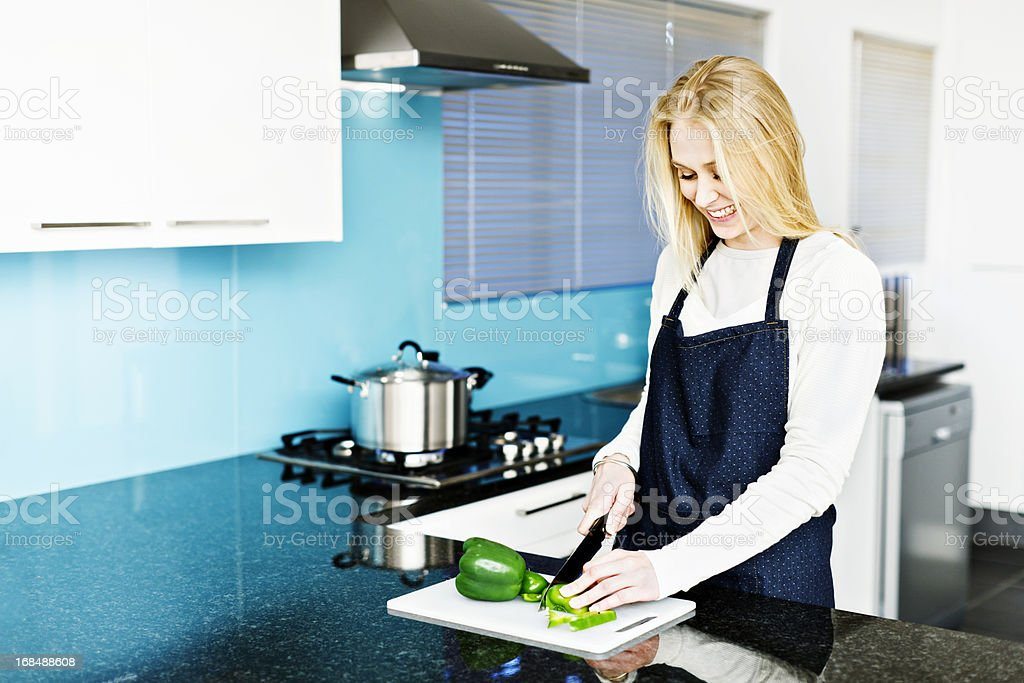 Happy young blonde smiles down,preparing food in modern kitchen royalty-free stock photo