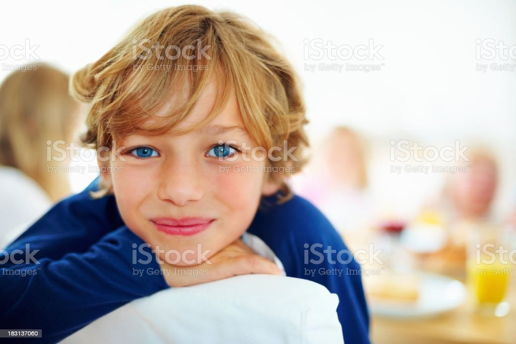 Happy young boy and his family having breakfast in background royalty-free stock photo