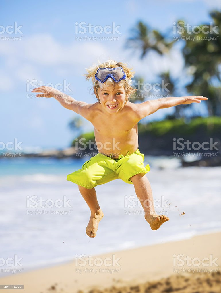 Happy young boy at the beach stock photo