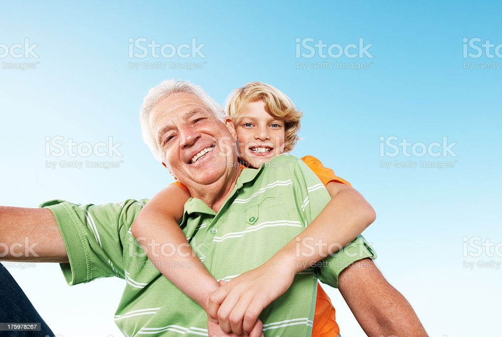 Happy young boy giving hug from back to his grandfather stock photo