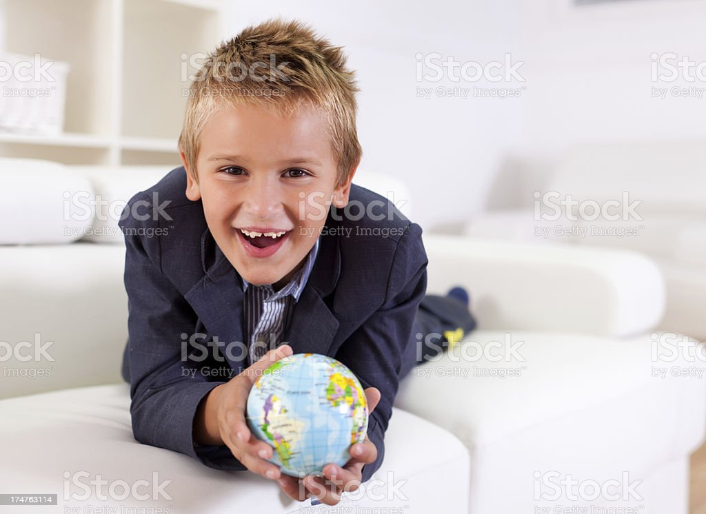 Happy young boy holding a globe royalty-free stock photo