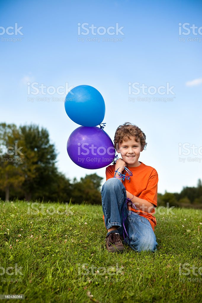 Happy Young Boy Holding Balloons Outside royalty-free stock photo