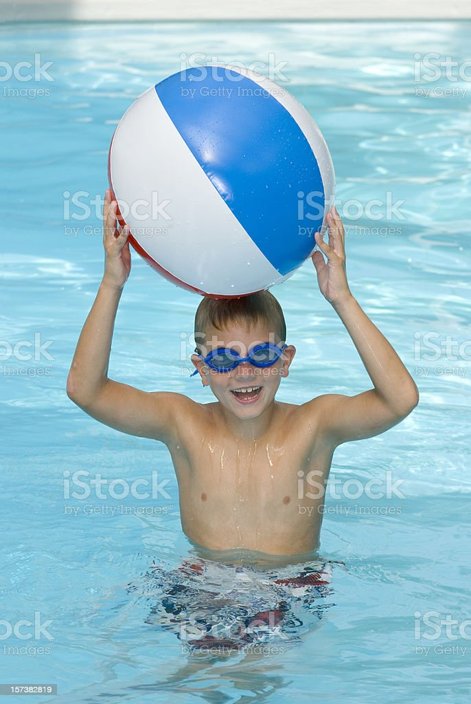 Happy Young Boy In Swimming Pool With A Beach Ball royalty-free stock photo