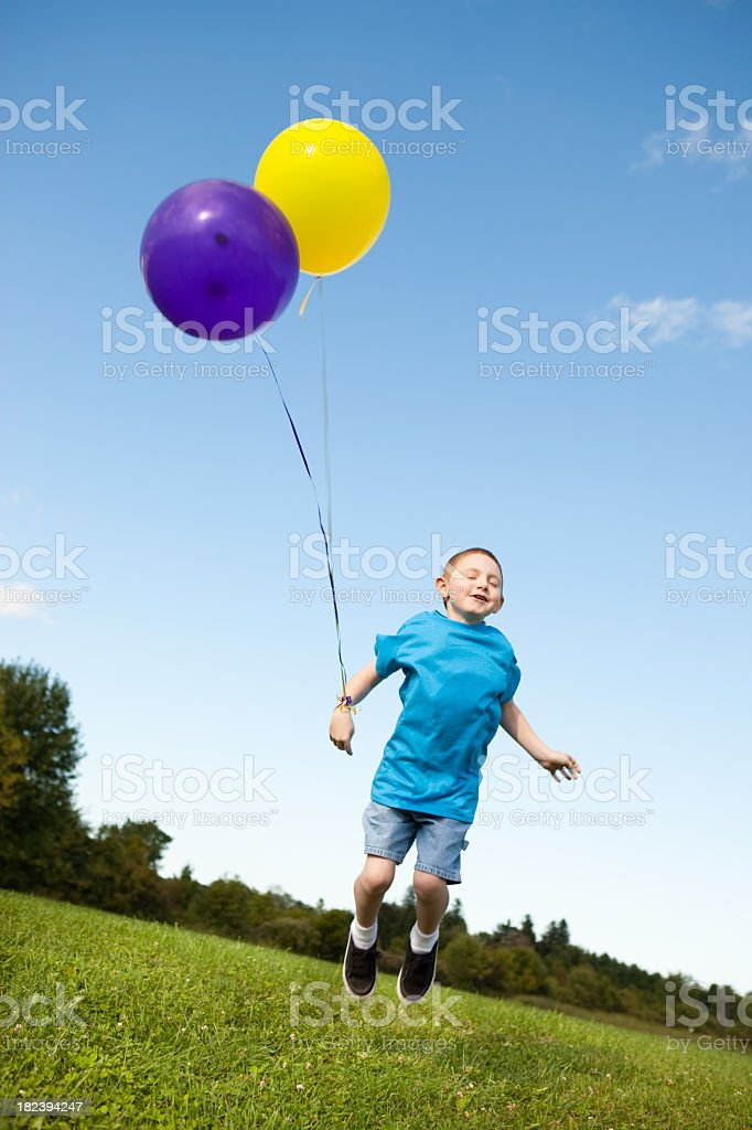 Happy Young Boy Jumping with Balloons Outside royalty-free stock photo