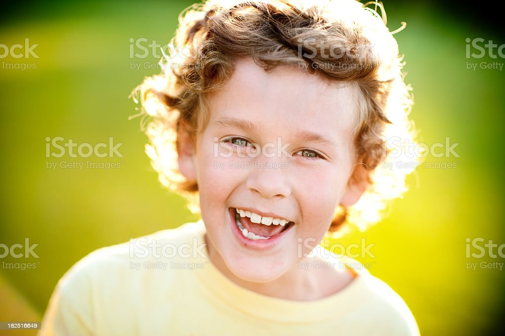 Happy Young Boy Laughing while Backlit by Evening Sun royalty-free stock photo