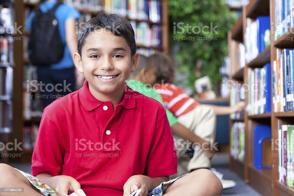 Happy young boy looking up while reading in school library stock photo