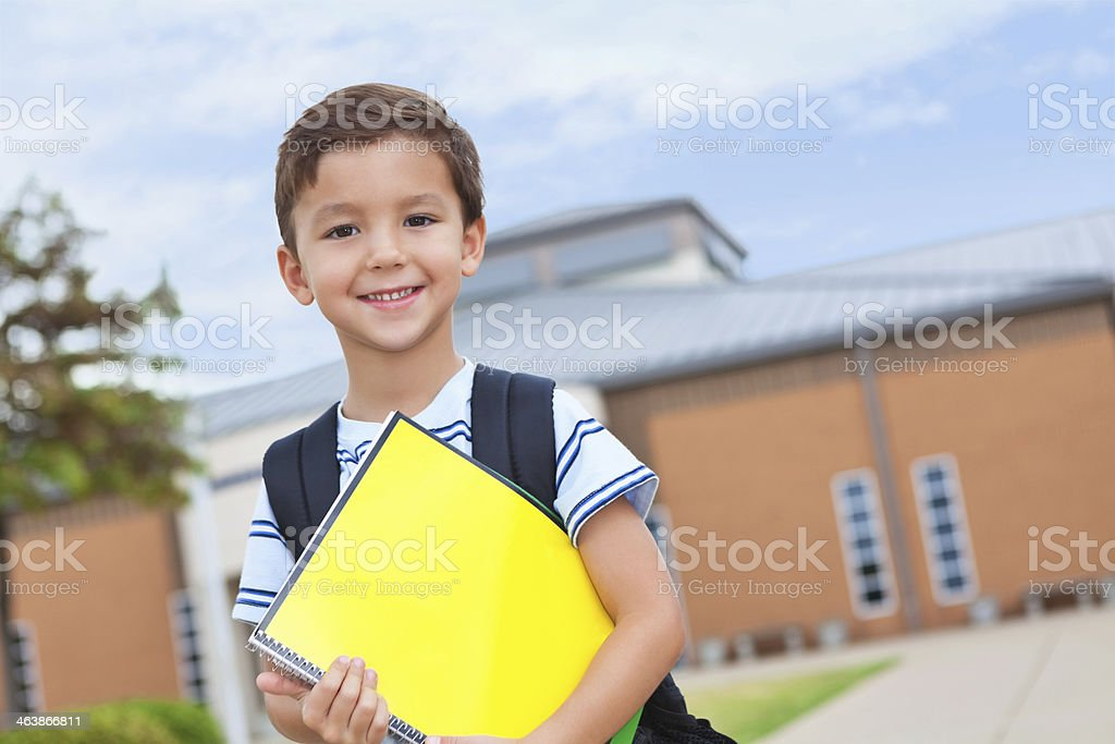 Happy young boy on campus ready for school stock photo