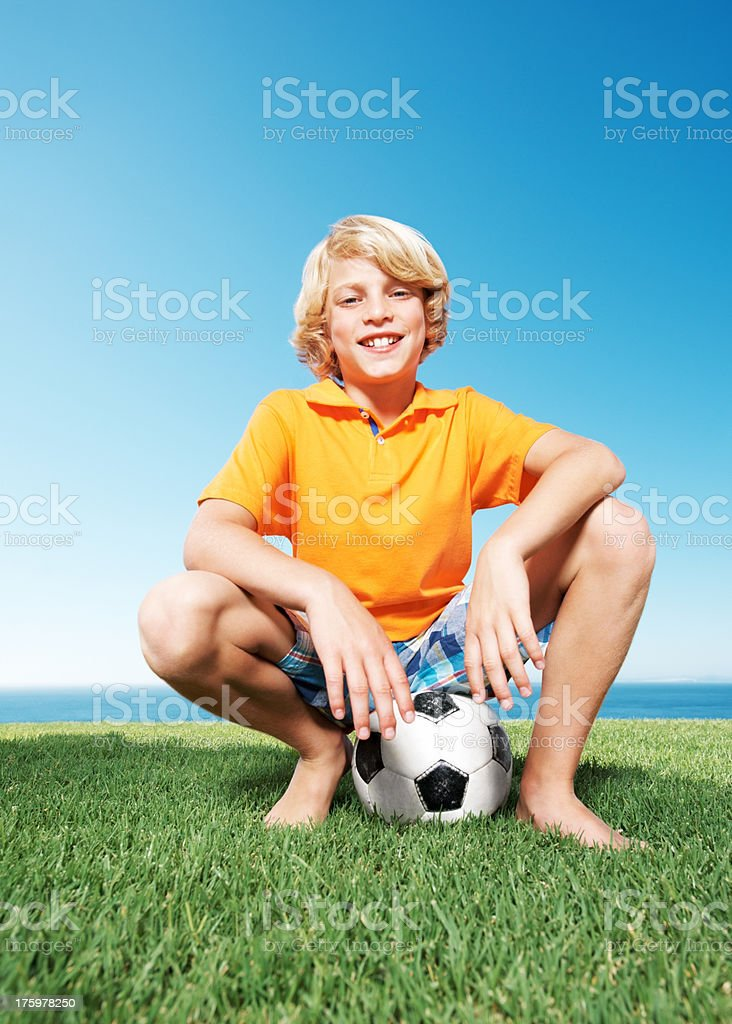 Happy young boy sitting on the football stock photo