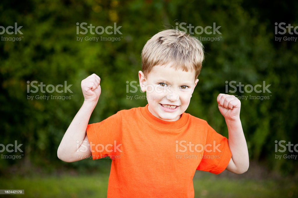 Happy Young Boy Smiling and Flexing Outside royalty-free stock photo