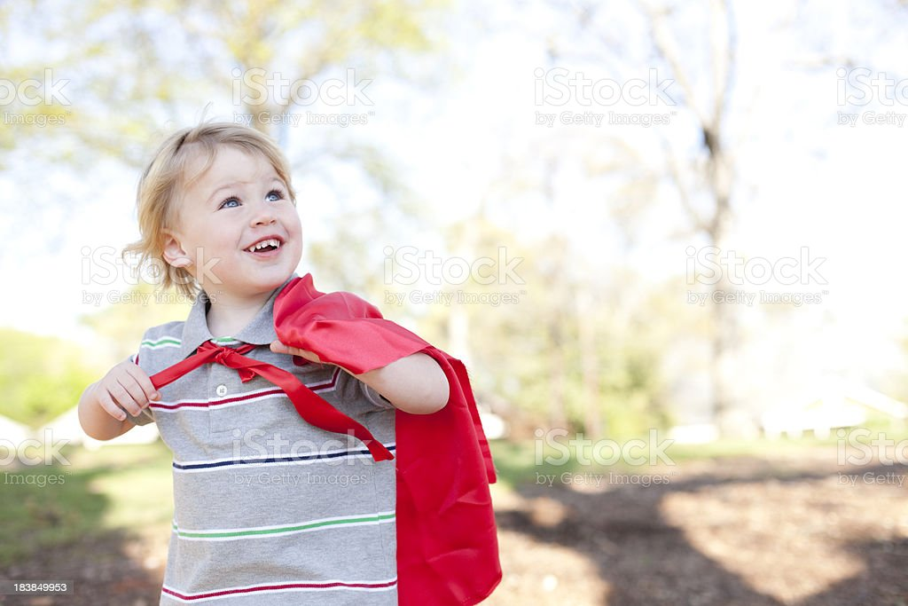 Happy young boy wearing red cape stock photo