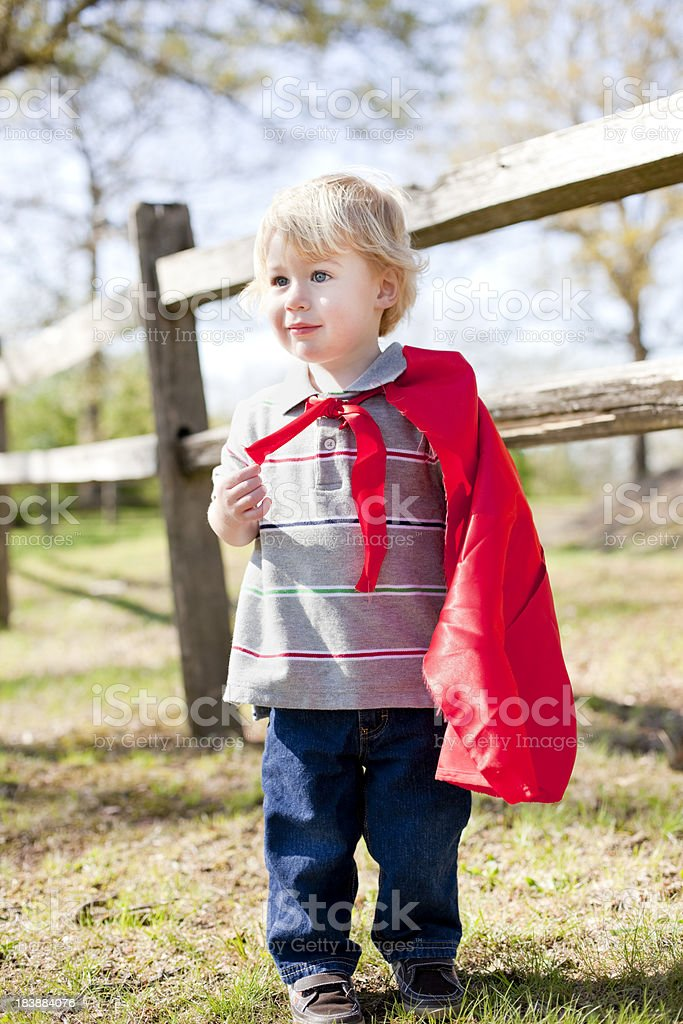 Happy young boy with a red cape at a park stock photo