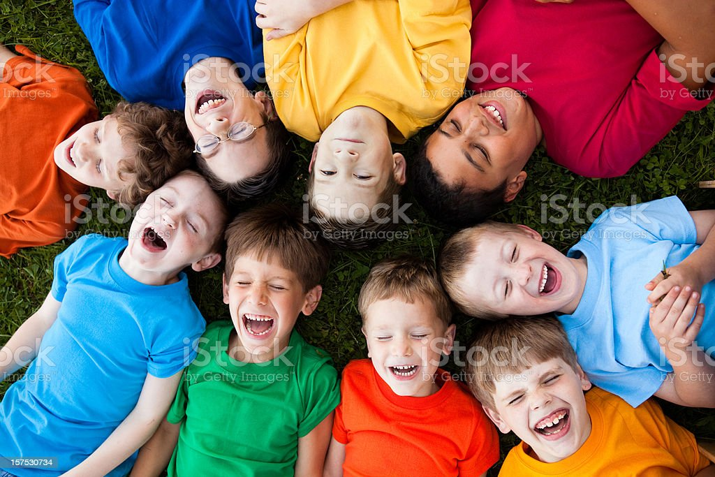 Happy Young Boys Laughing While Lying in a Circle Outside royalty-free stock photo