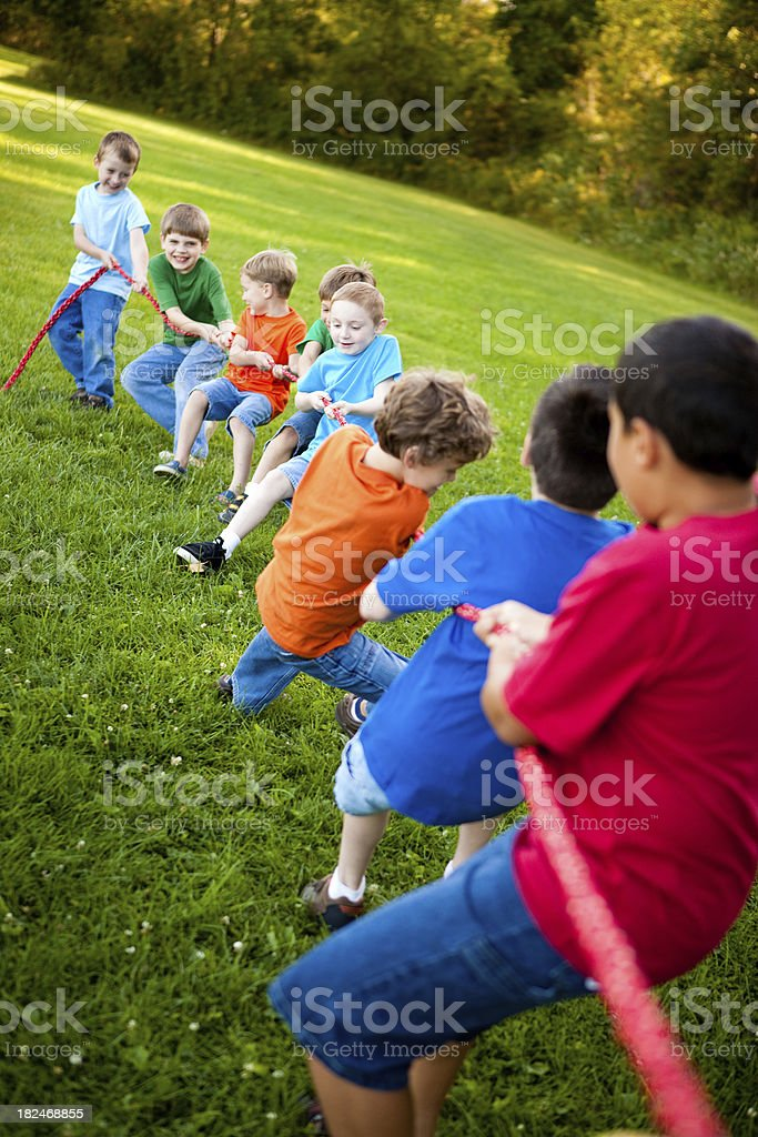 Happy Young Boys Playing Tug-of-War Outside royalty-free stock photo