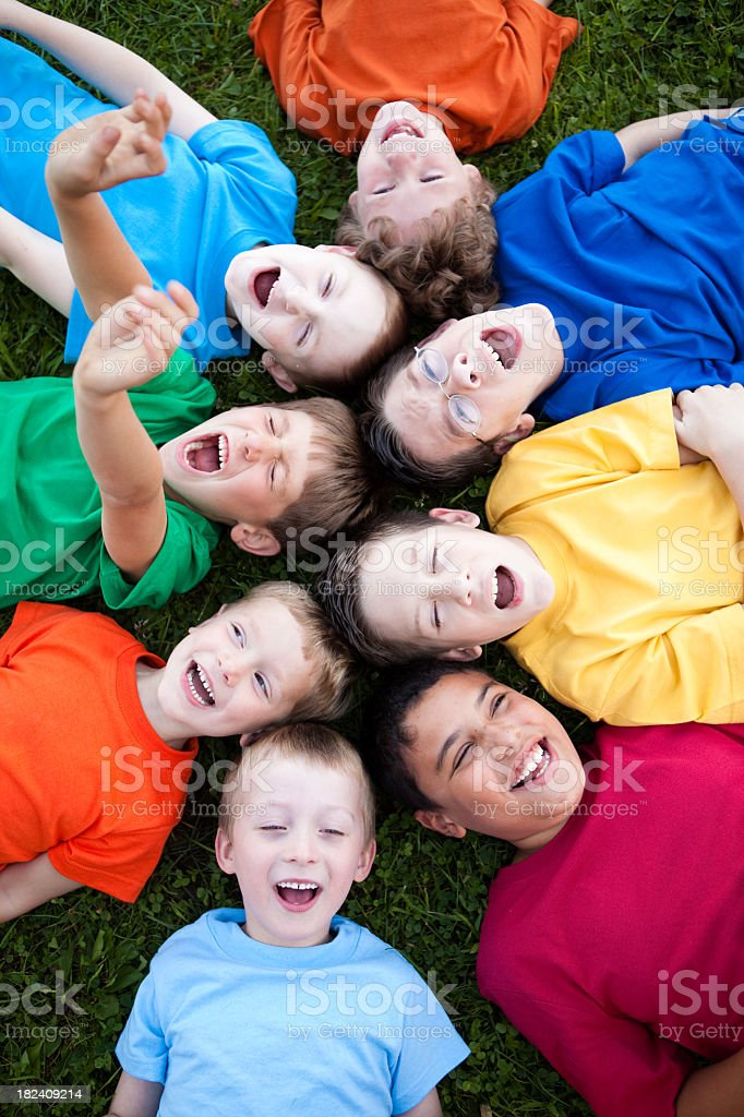 Happy Young Boys Yelling While Lying in a Circle Outside royalty-free stock photo