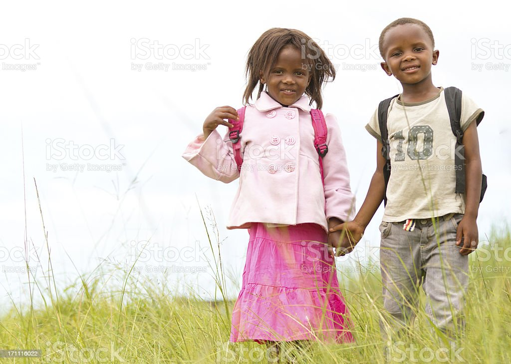 Happy young brother and sister going to school in Africa stock photo