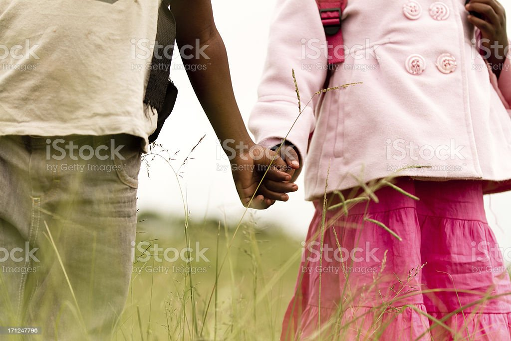 Happy young brother and sister holding hands stock photo