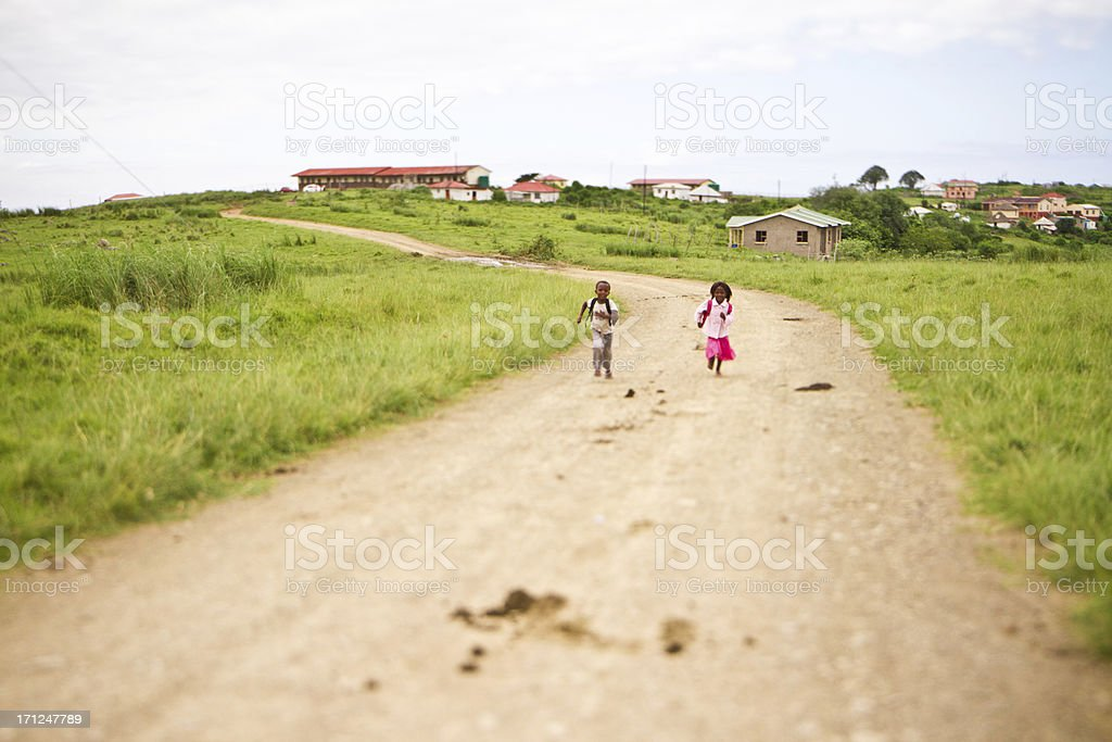 Happy young brother and sister running to school together stock photo
