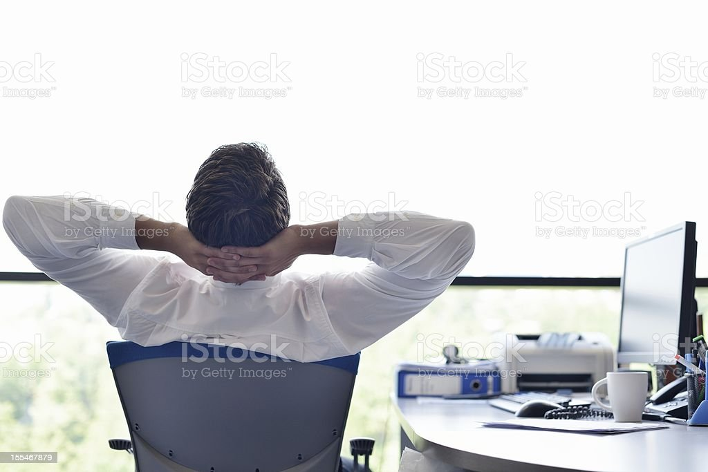 A happy young business man relaxing at his office stock photo