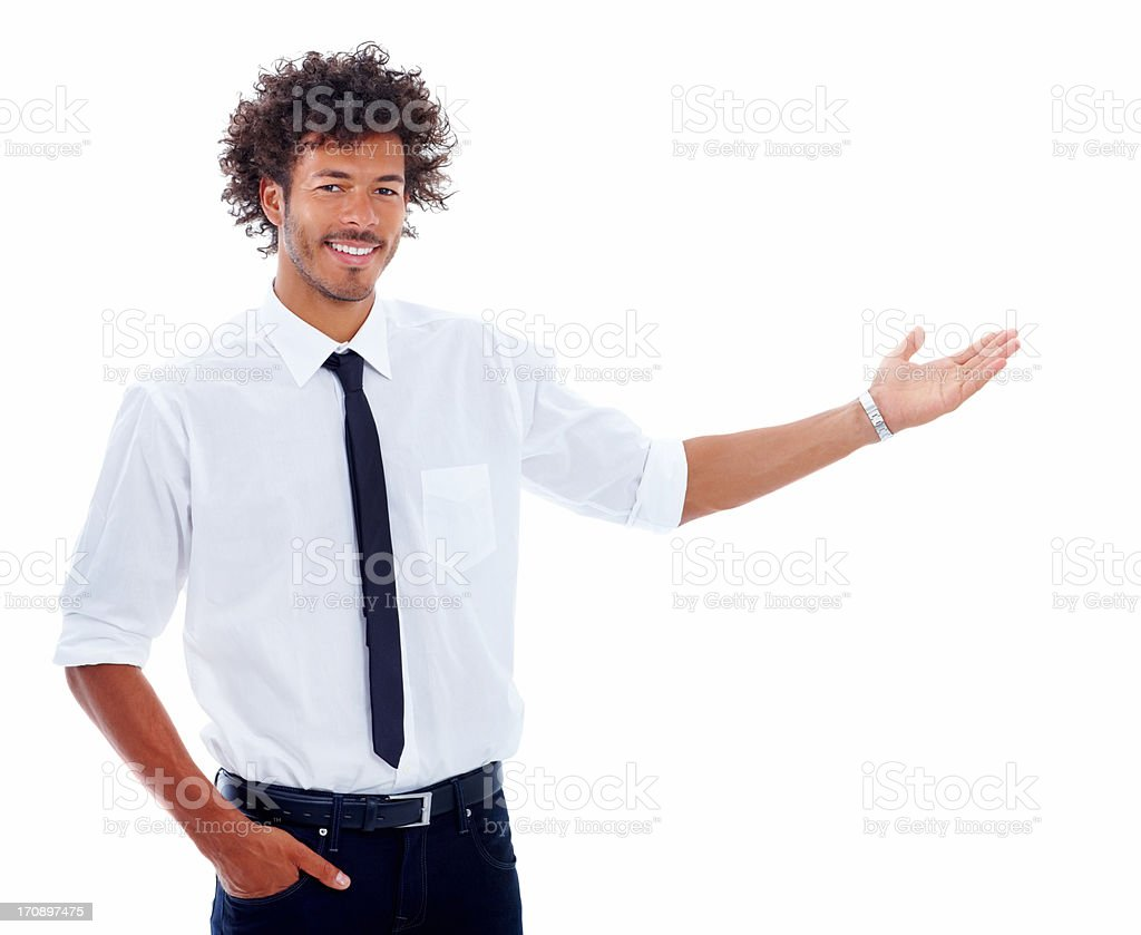 Happy young business man with hand outstretched for presentation stock photo