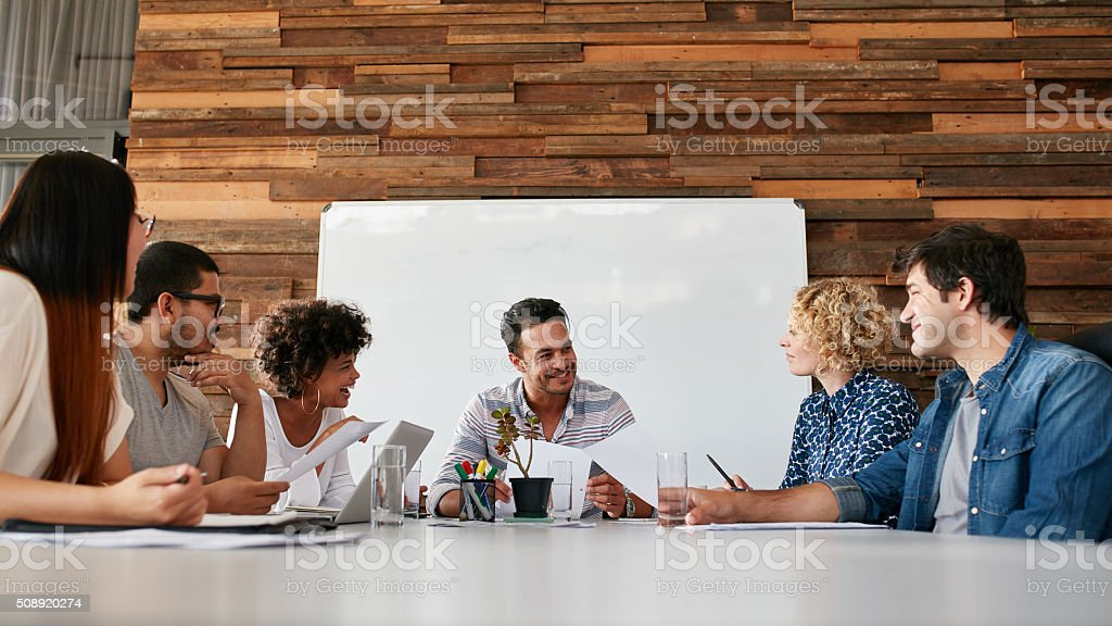 Happy young business people meeting in conference room stock photo