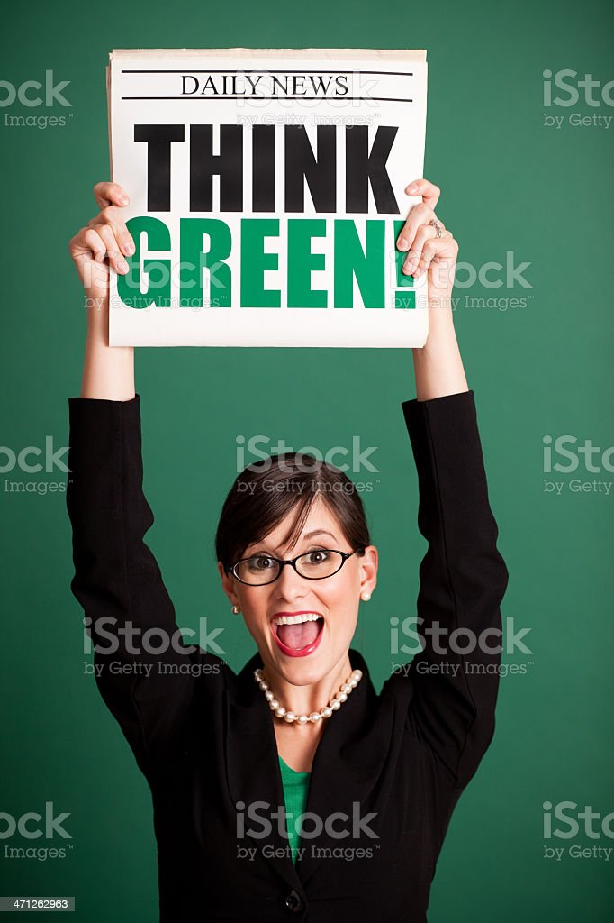 Happy Young Business Woman Holding Newspaper Headlined 'Think Green!' stock photo