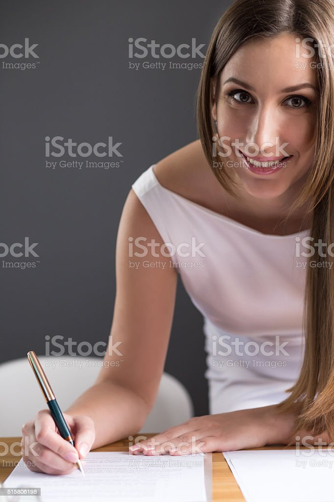 Happy young business woman signing document stock photo